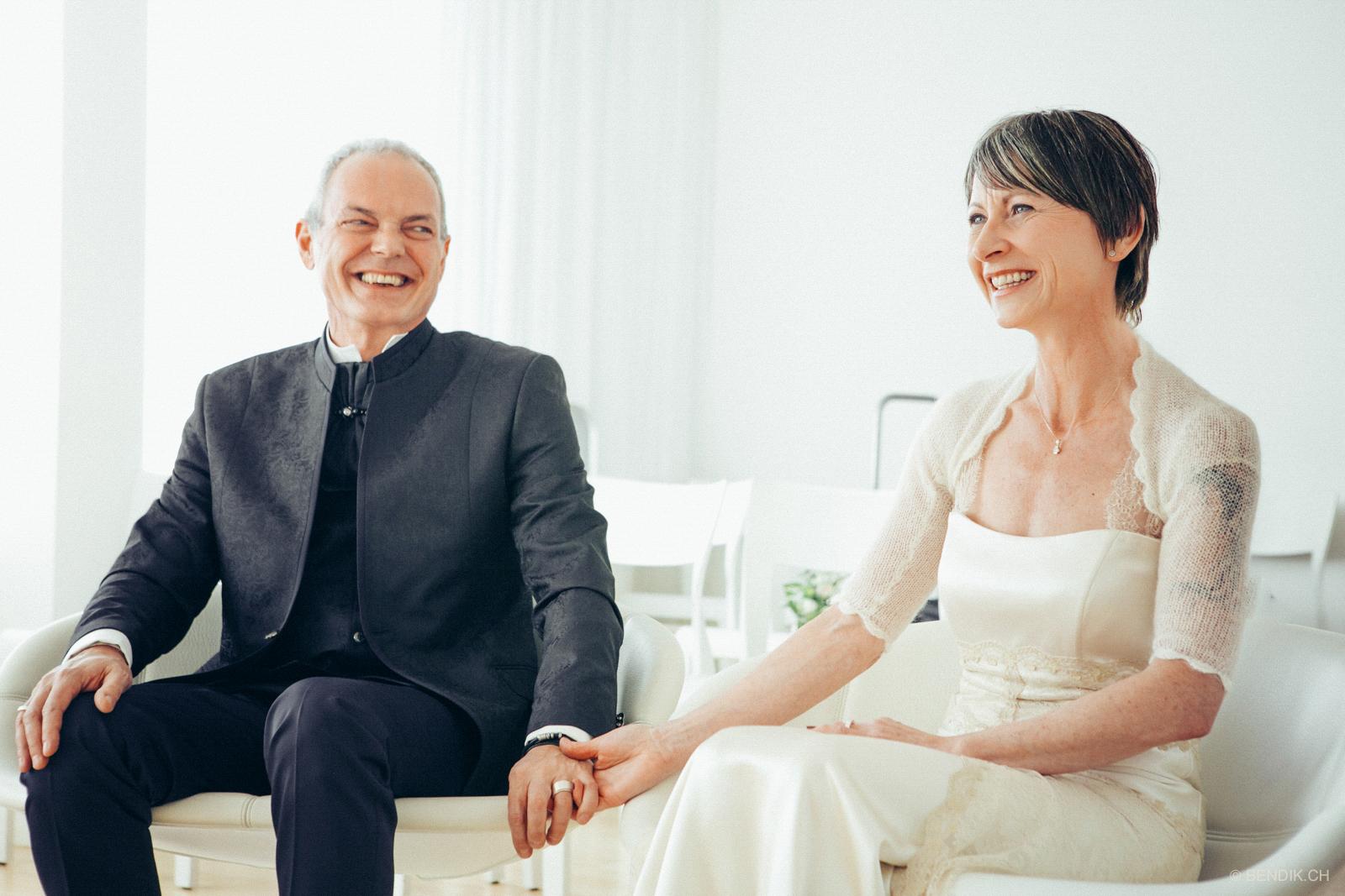 Lachendes Brautpaar hält sich an den Händen
