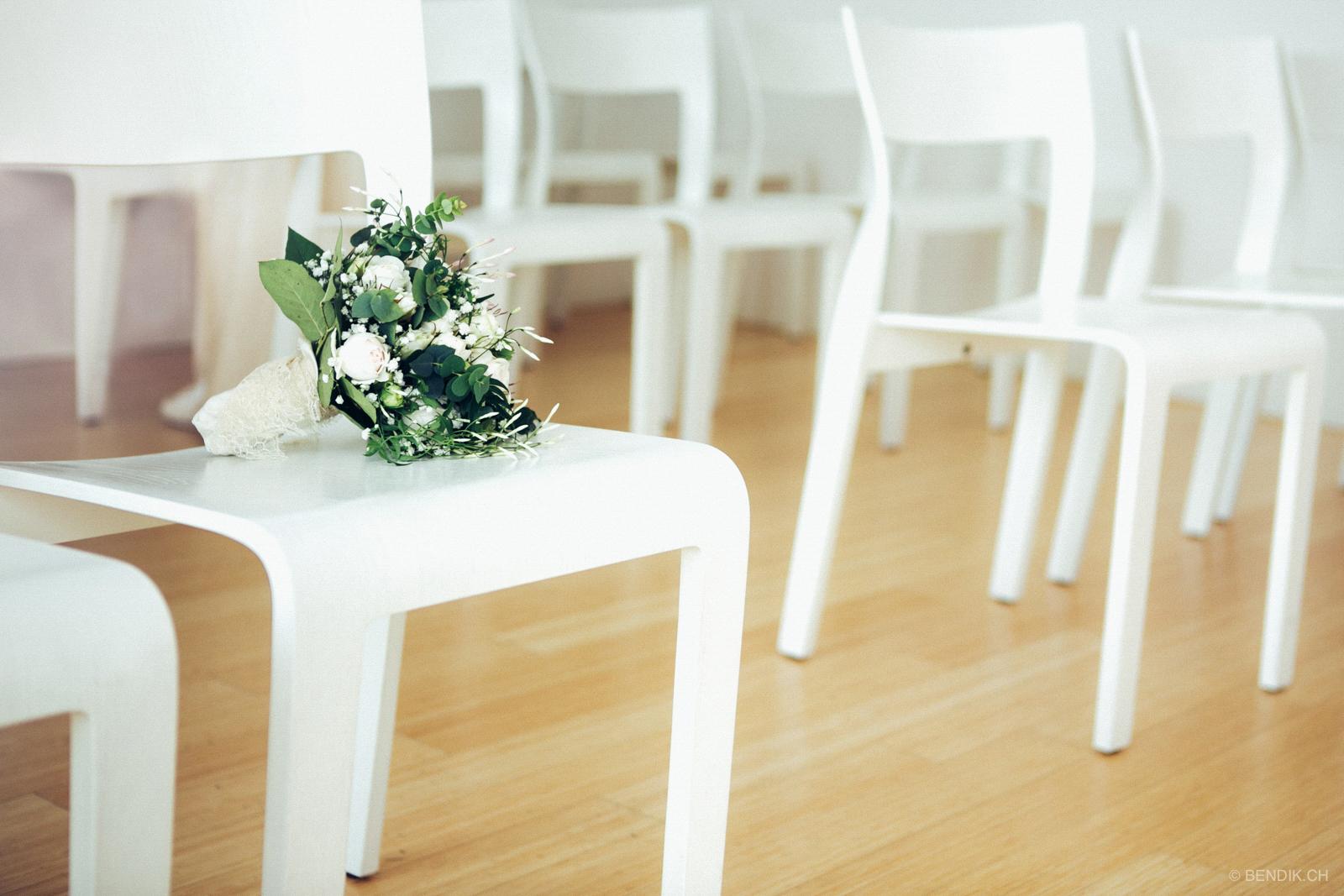 Weisse Stühle im Trauzimmer mit grün-weissem Brautstrauss