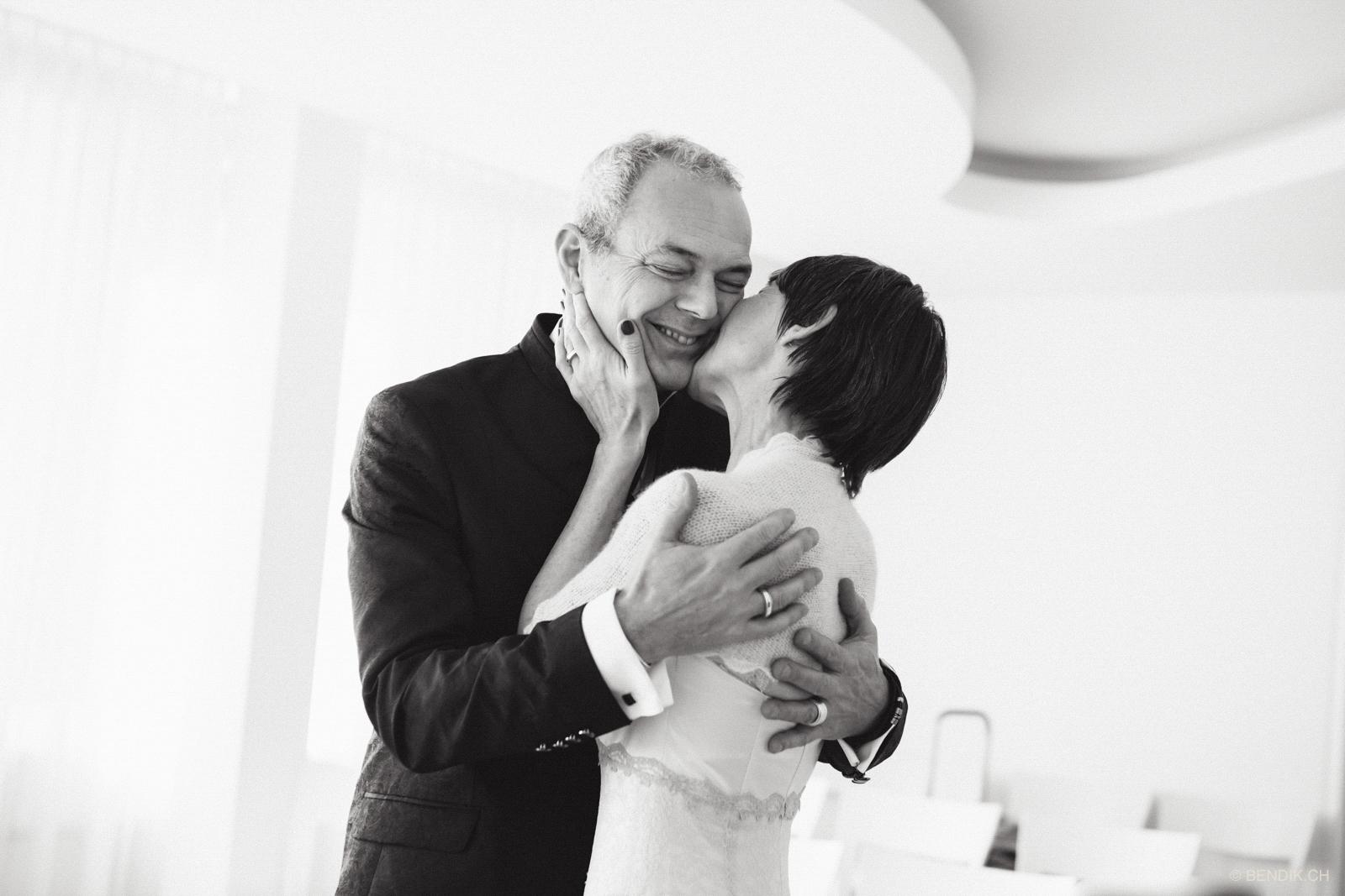 Schwarz-weiss Aufnahme der Braut, wie sie den Bräutigam auf die Wange küsst