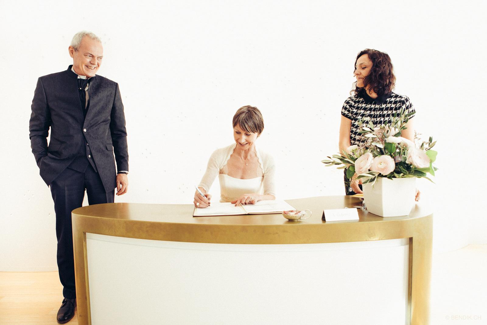 Braut unterschreibt lachend Eheurkunde