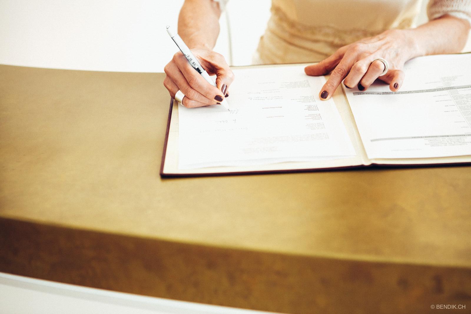 Grossaufnahme der Braut beim Unterschreiben der Eheurkunde
