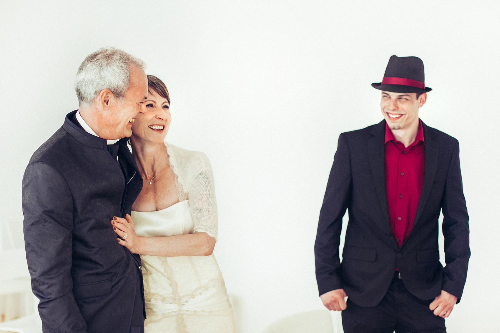 Brautpaar umarmt sich während Trauzeuge lachend danebensteht