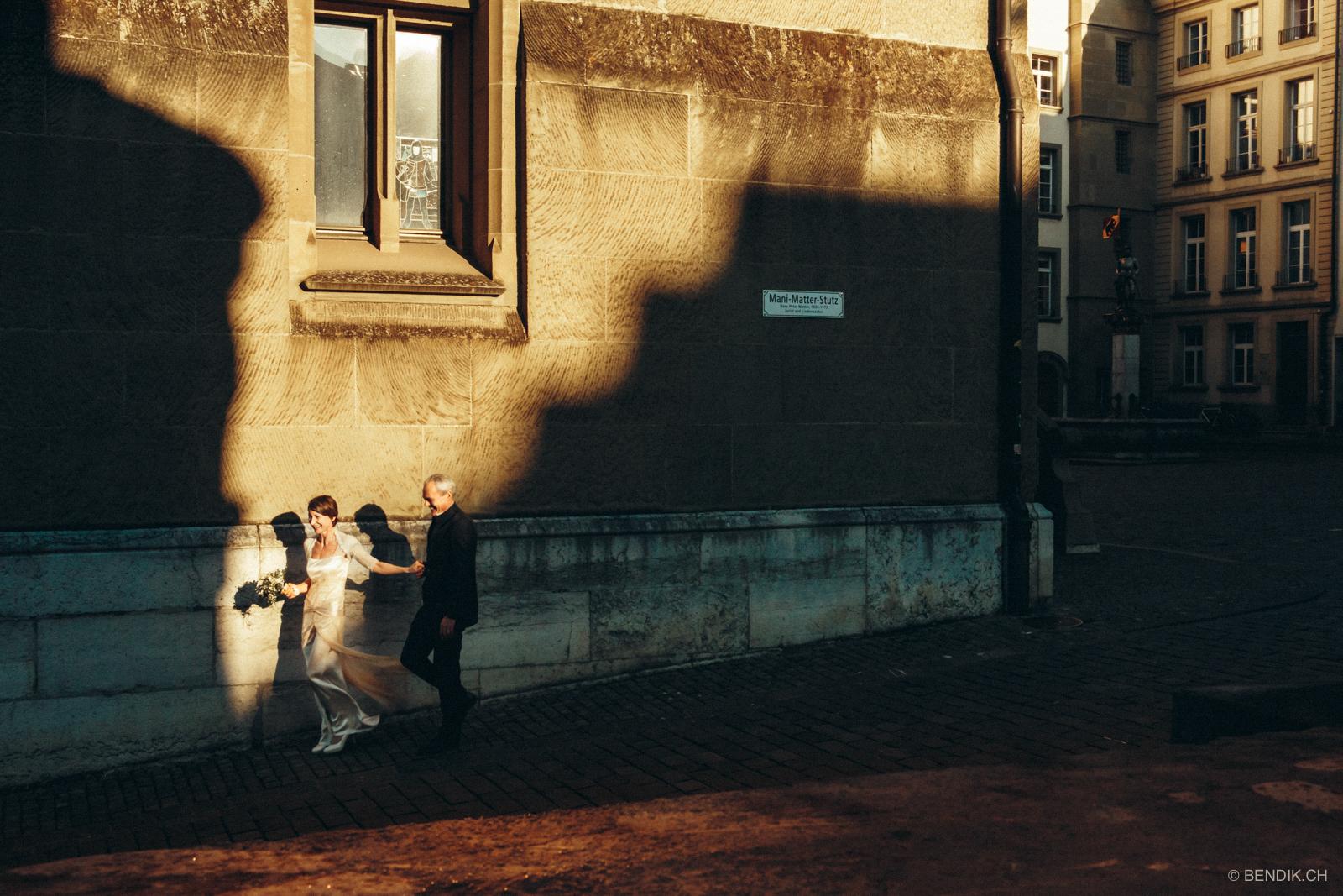 Brautpaar läuft lachend einen Weg in Bern entlang