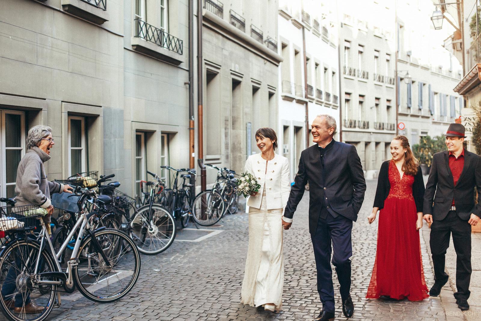 Passantin mit Fahrrad gratuliert lachend frischvermählten Brautpaar in Bern