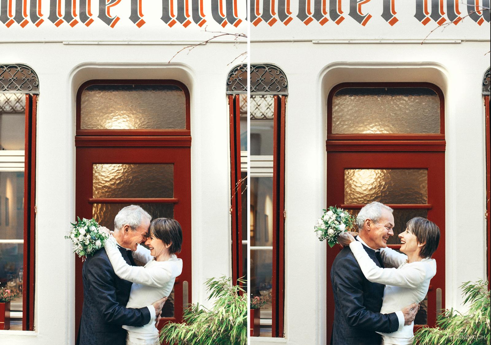Braut mit Braustrauss stützt Arme auf Schultern des Bräutigams ab