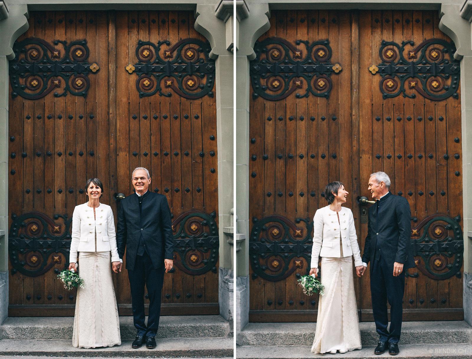 Brautpaar sieht lachend in die Kamera vor grossem, hölzernen Tor