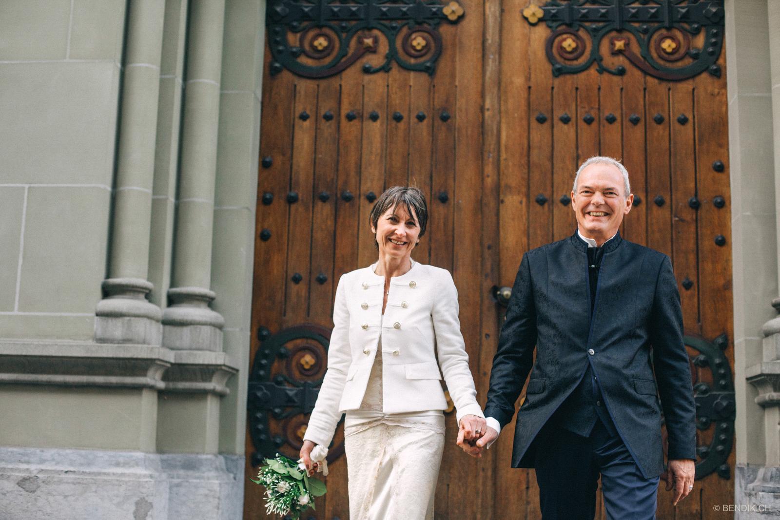 Brautpaar hält sich an der Hand und schreitet lachend in Richtung Kamera in Bern
