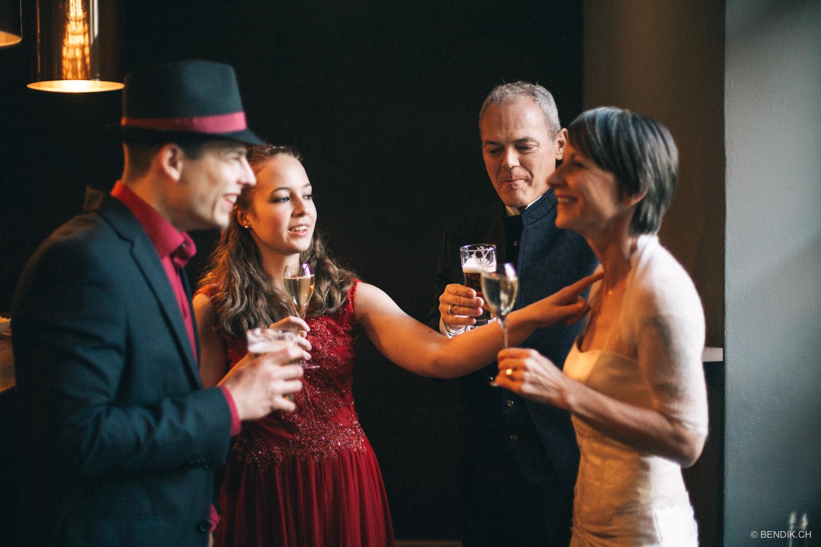Brautpaar und Trauzeugen mit Sekt lachend während Apéro