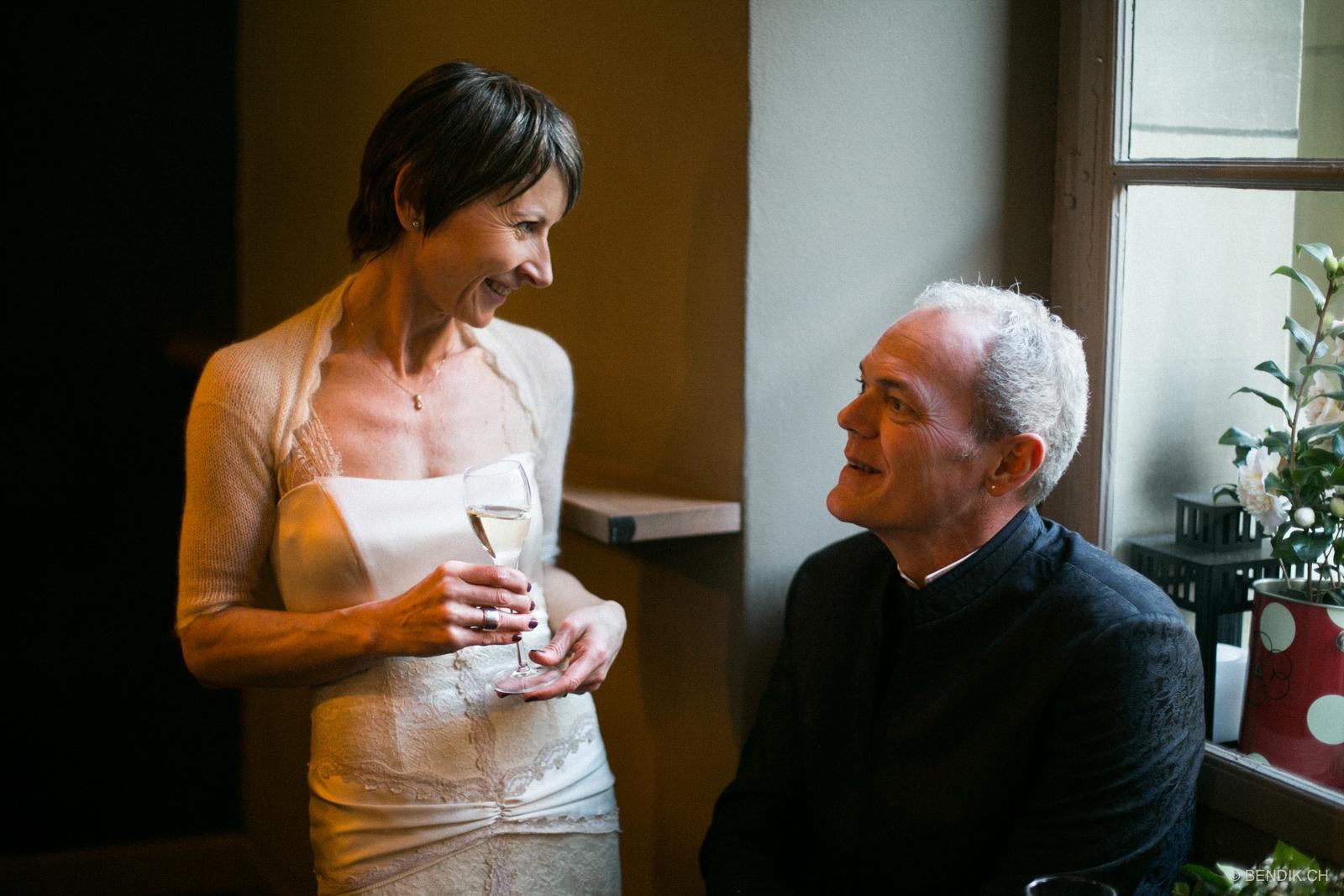 Brautpaar in angeregter Diskussion bei einem Glas Sekt