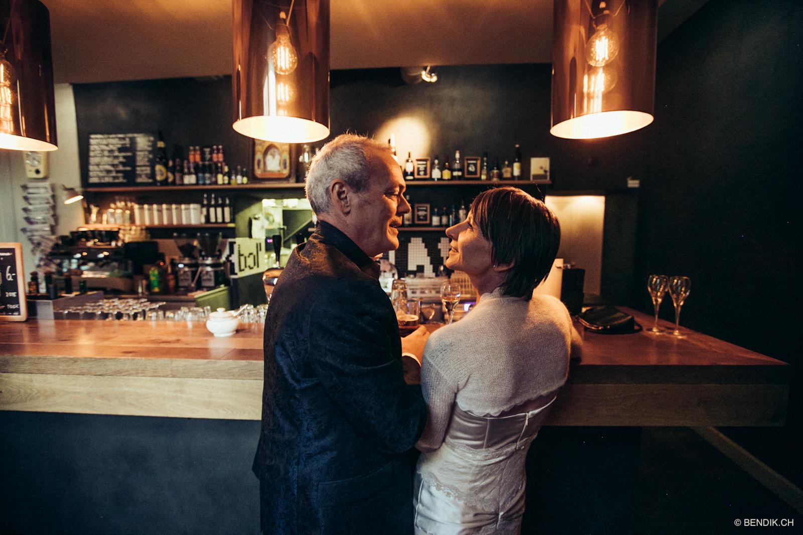 Brautpaar sieht sidh lächend am Tresen an