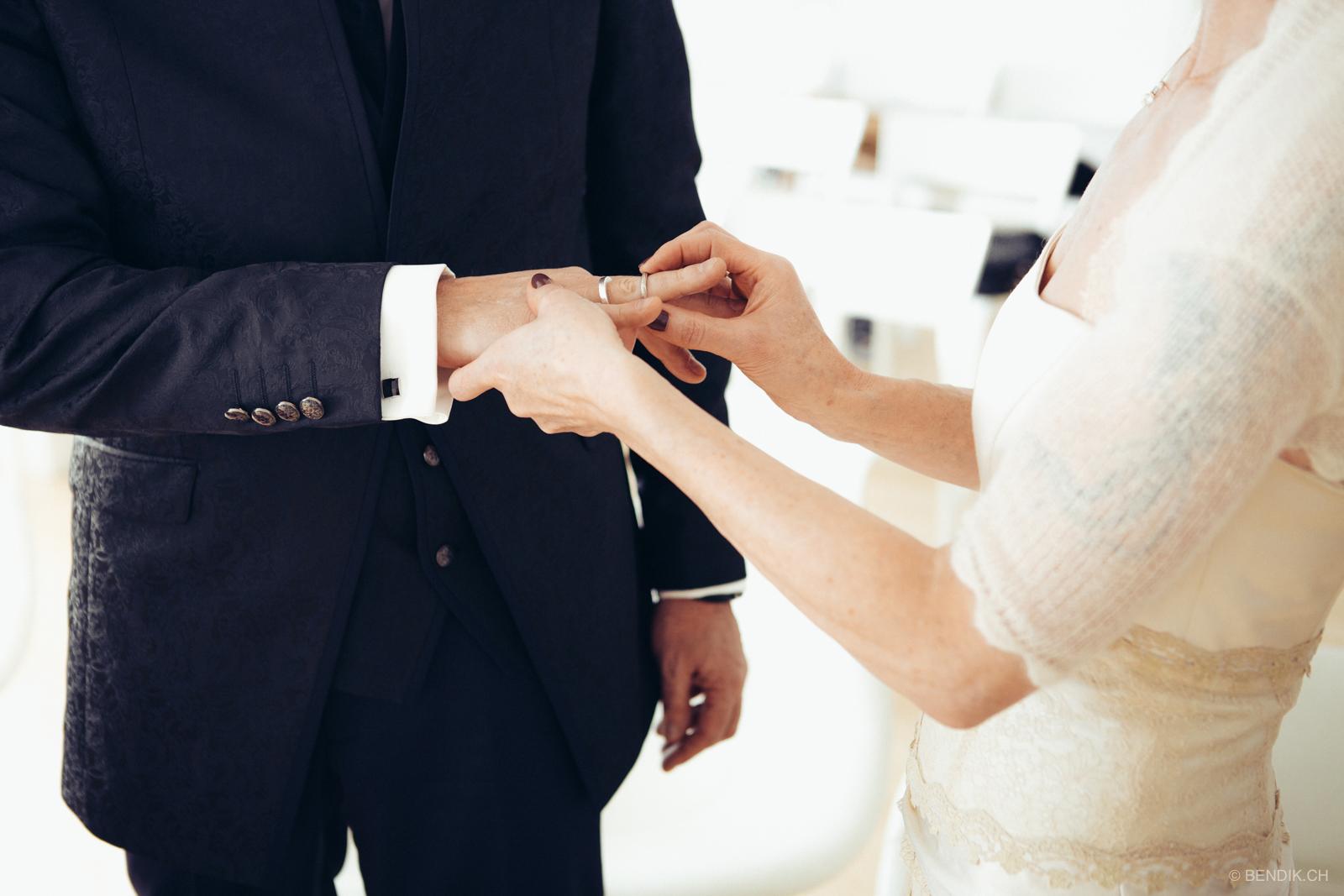 Braut steckt Bräutigam Trauring an