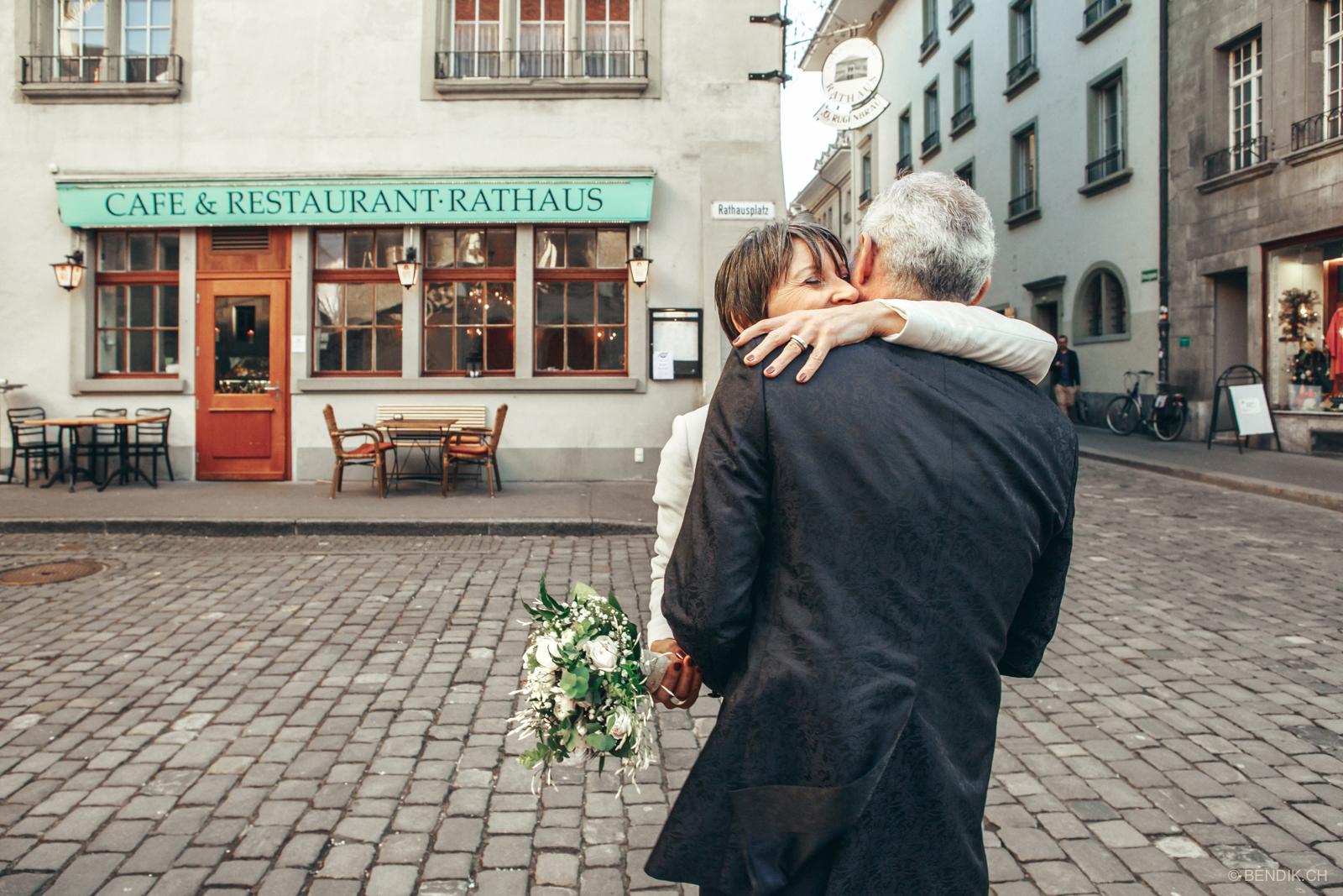 Brautpaar umarmt sich mit kleinem Kaffeehaus im Hintergrund