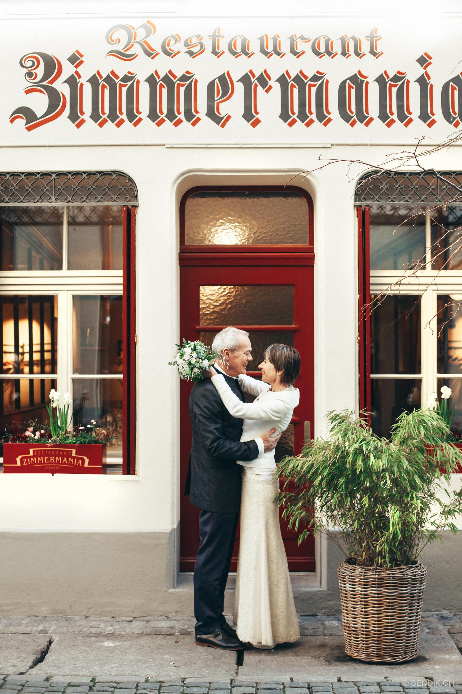 Lachendes Brautpaar vor roter Eingangstüre in Bern