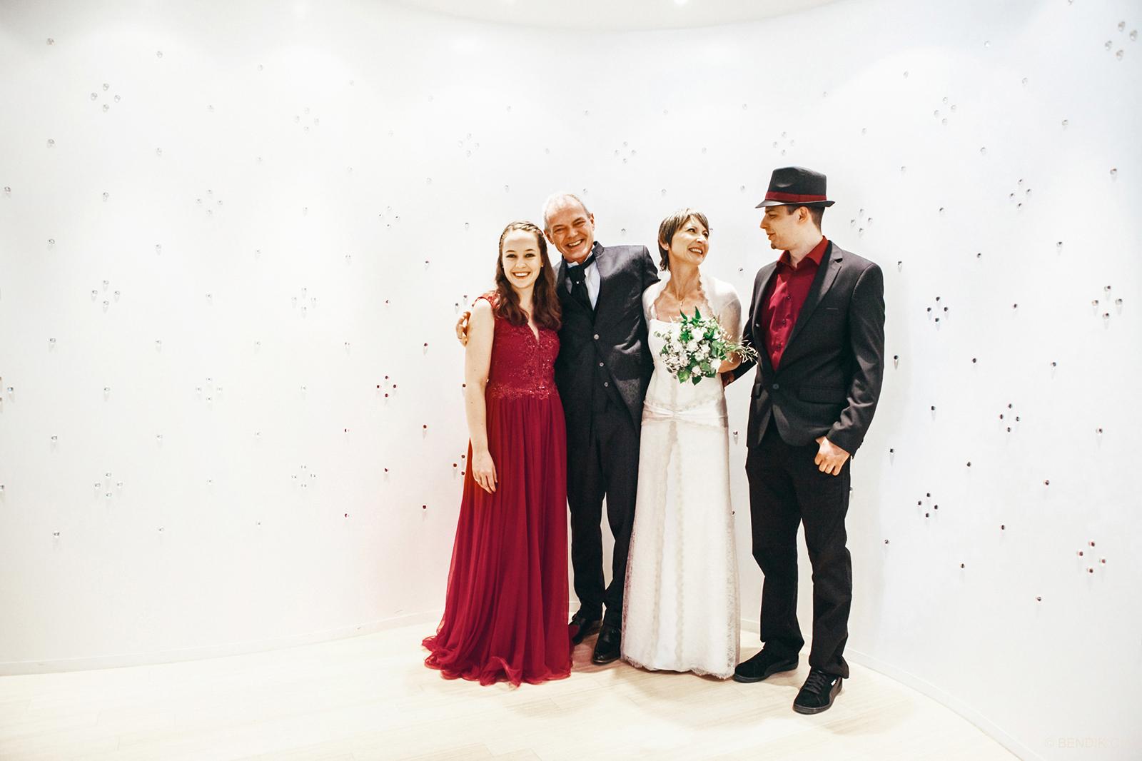 Lachende Hochzeitsgesellschaft vor weissem Hintergrund