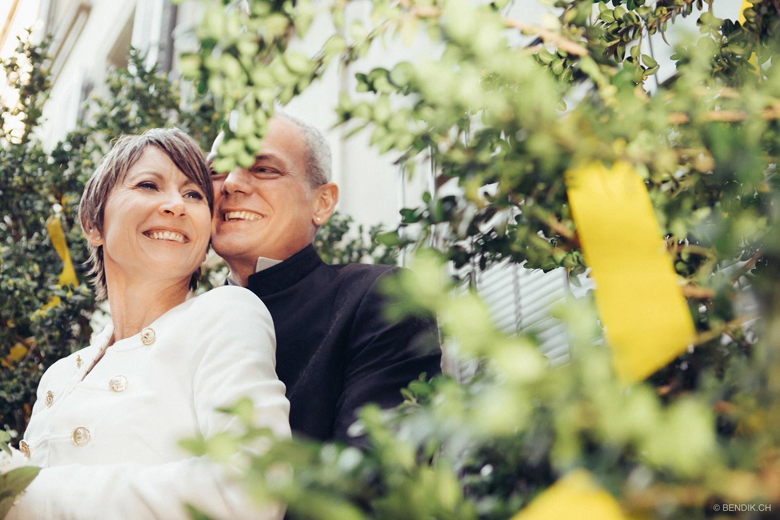 Brautpaar sich umarmend und lachend inmitten von Blumen