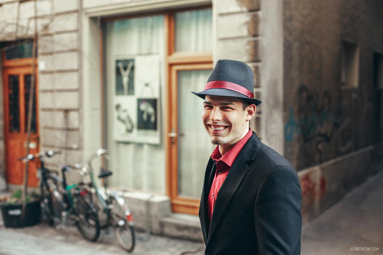 Trauzeuge mit schwarz-rotem Hut und Anzug schaut lachend in die Kamera