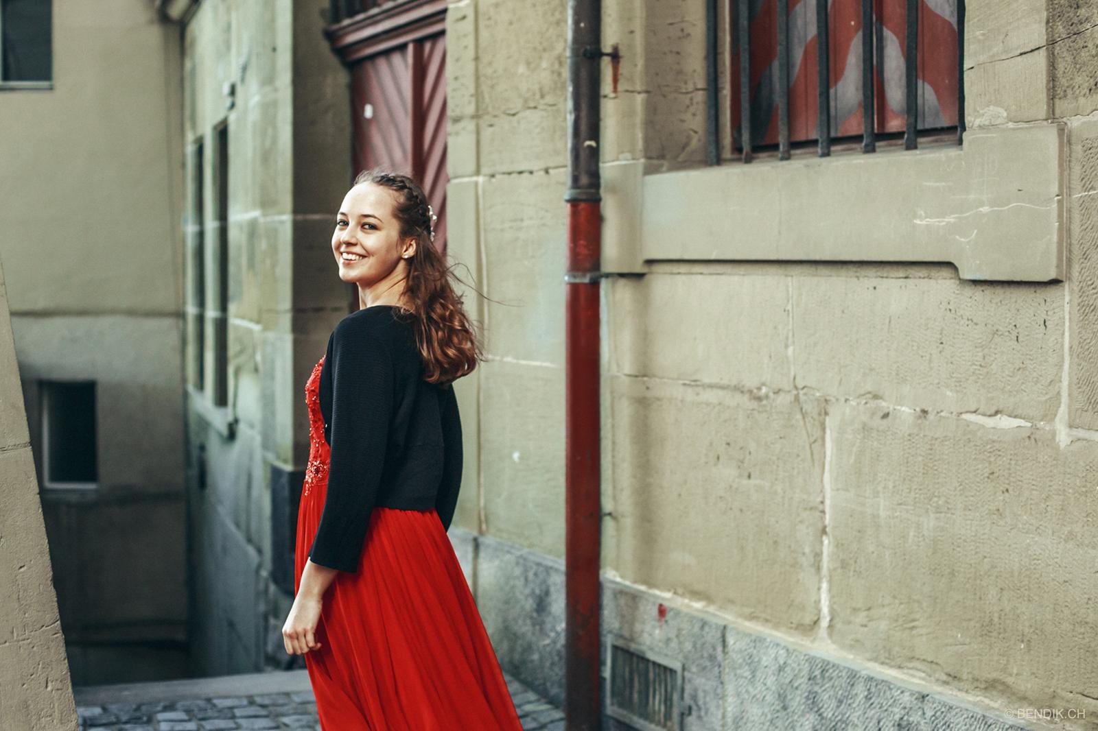 Trauzeugin in schwarz-rotem Kleid sieht über Schulter lachend in die Kamera