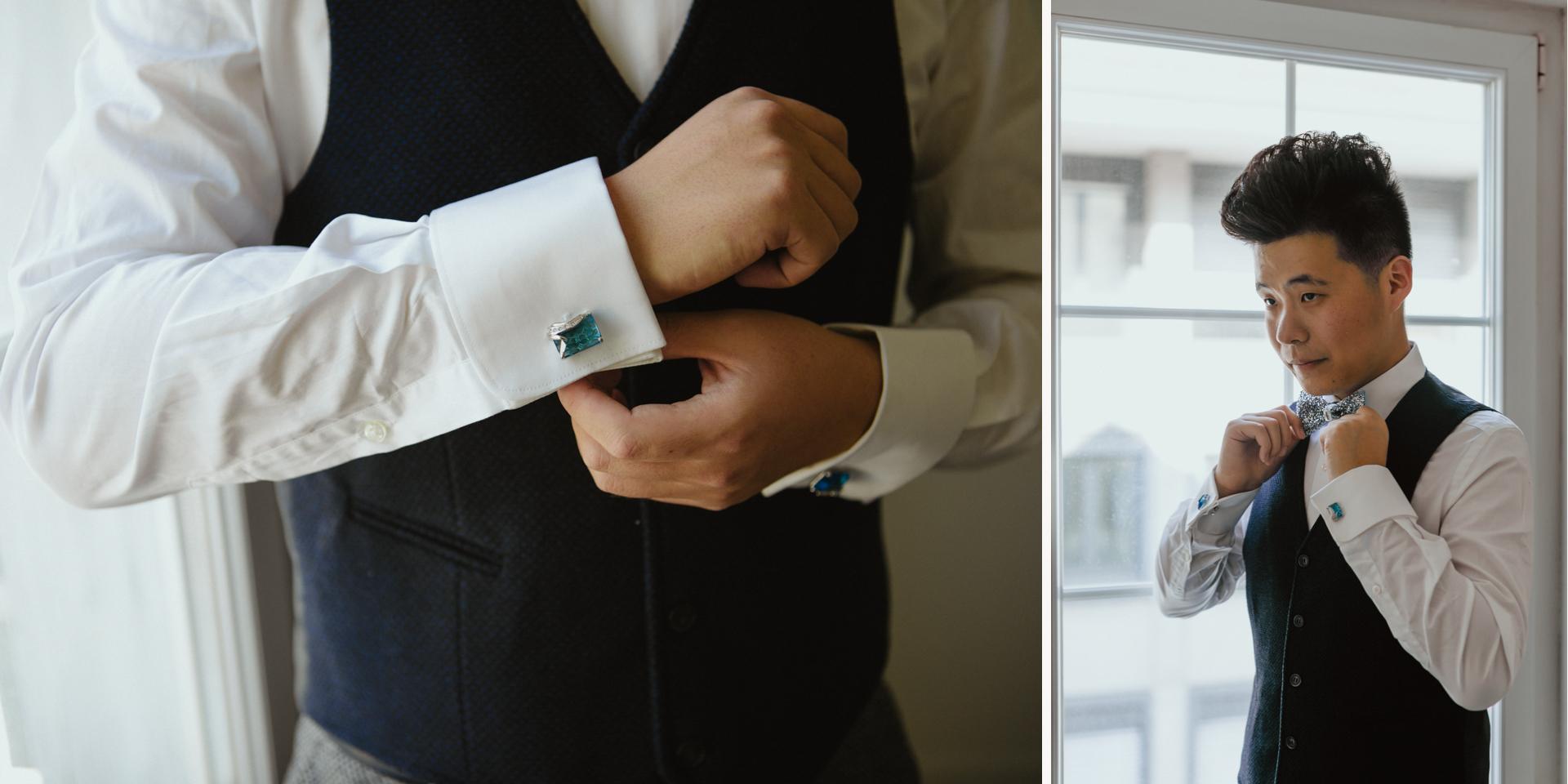 Bräutigam richtet sich Fliege und hält Manschettenknöpfe in die Kamera