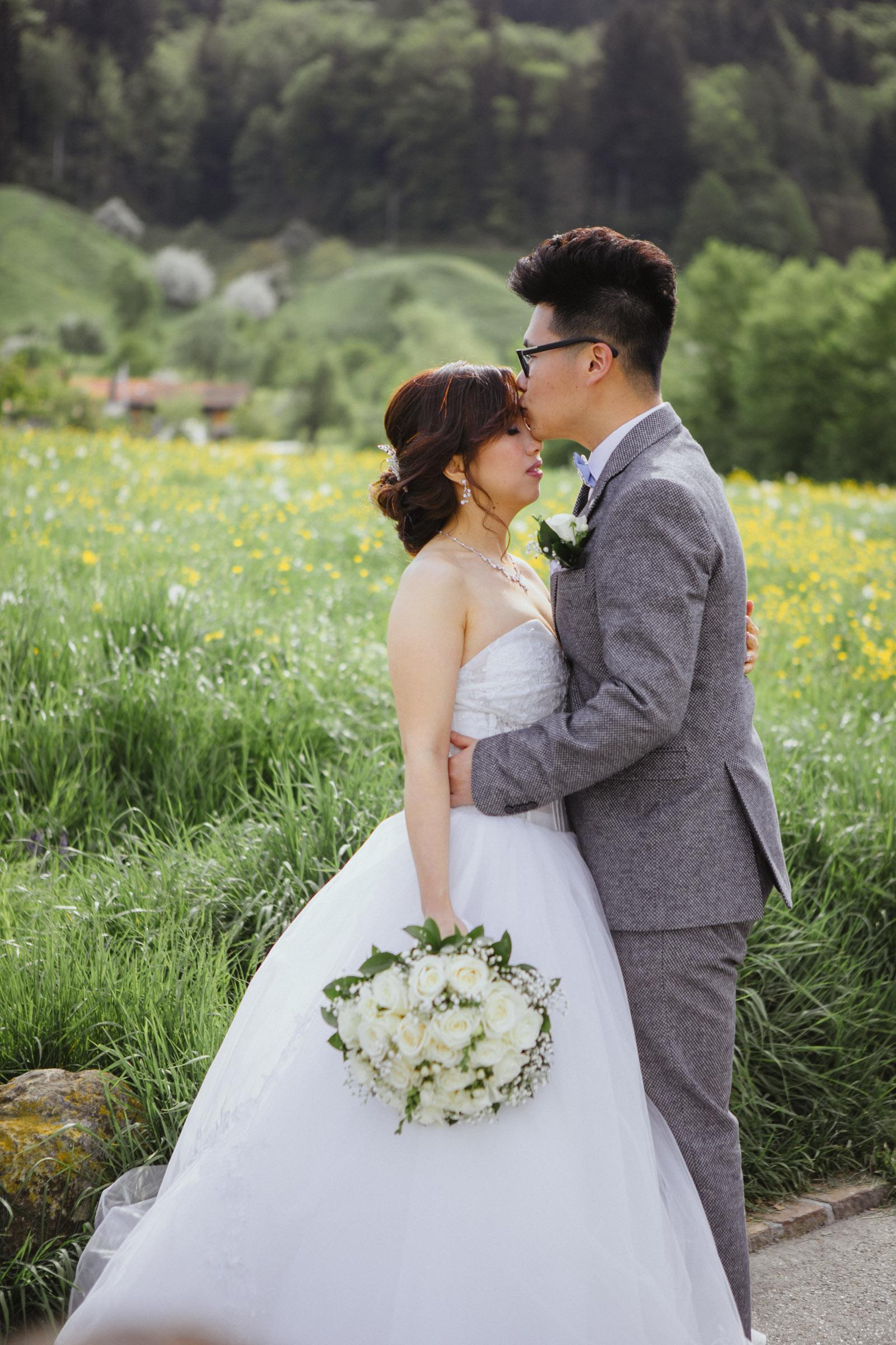 Bräutigam küsst Braut auf Stirn vor grüner Wiese in der Umgebung Zug