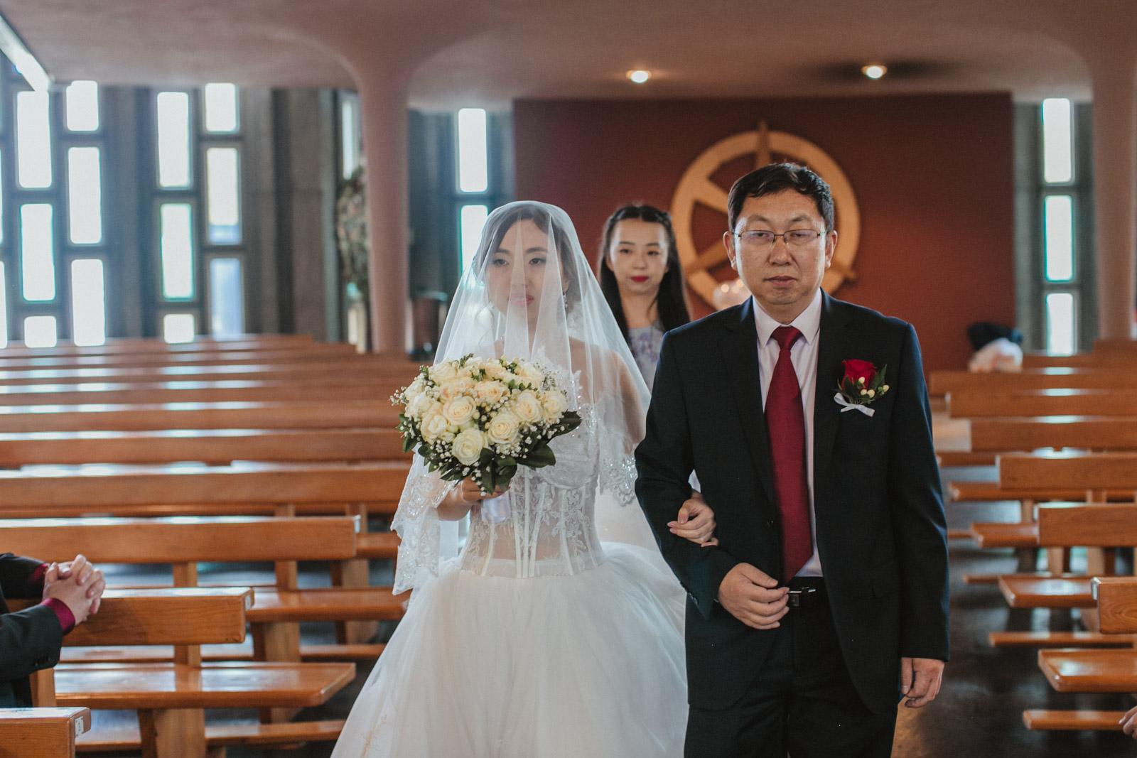Vater führt verschleierte Braut zum Altar