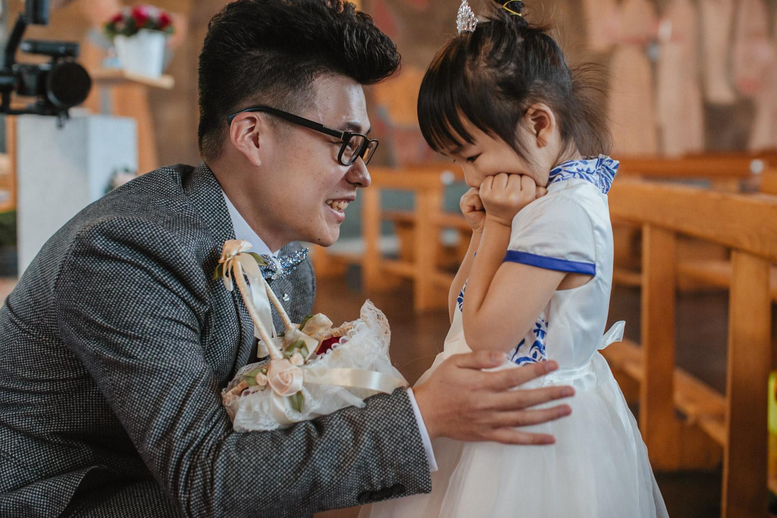 Bräutigam ermutigt Blumenmädchen lächelnd
