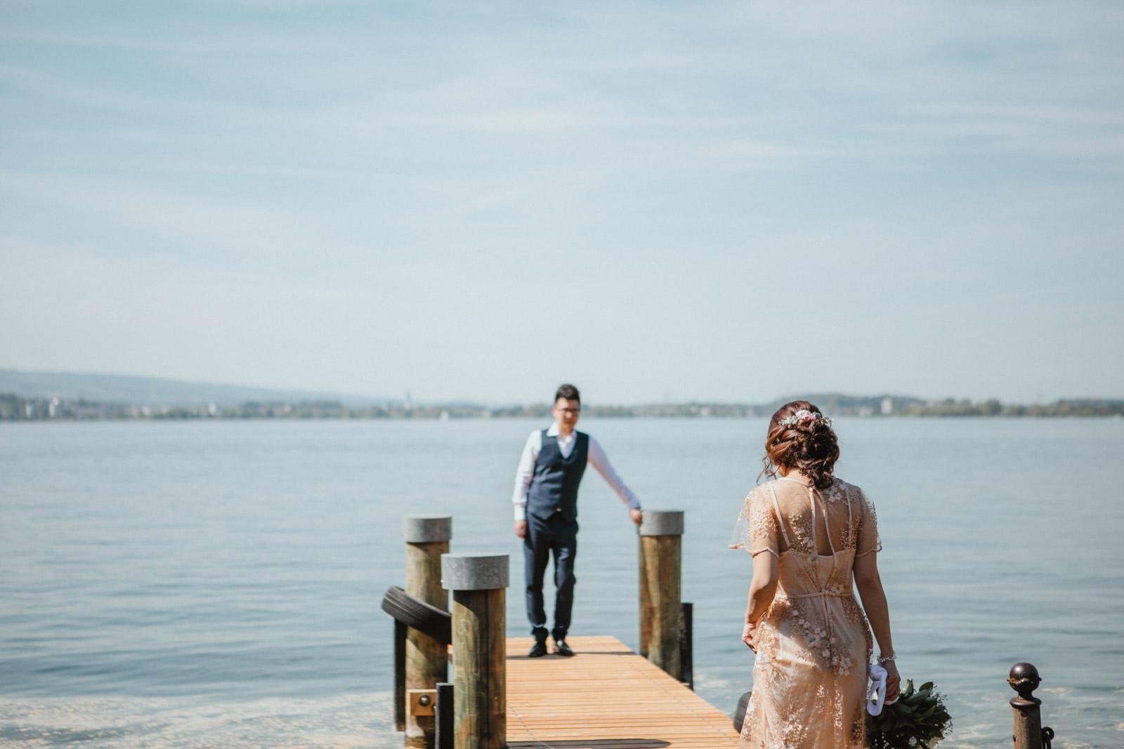 Bräutigam wartet auf Braut mit Brautstrauss vor Zugersee