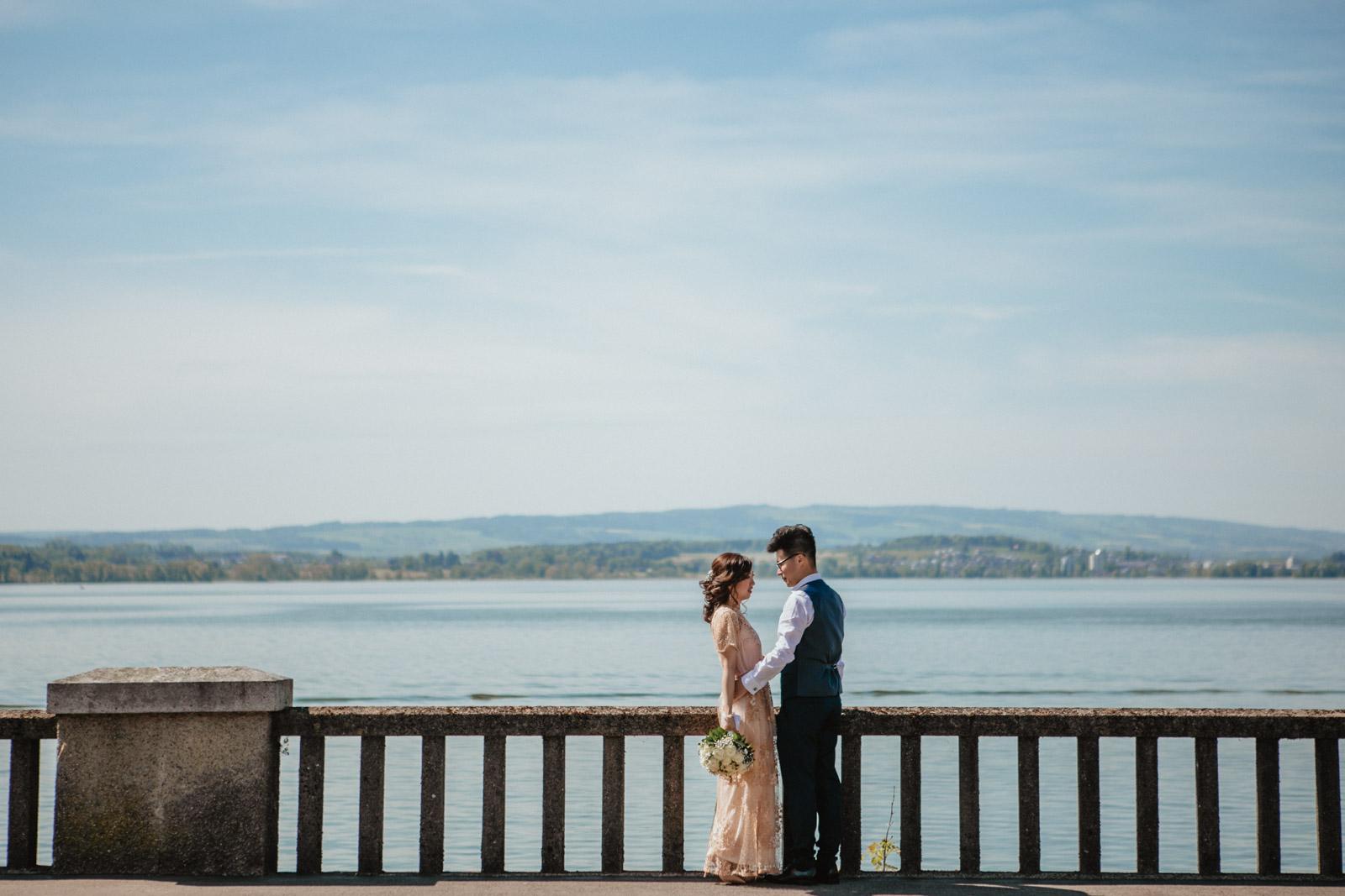Bräutigam legt Hand auf Hüfte der Braut vor Zugersee