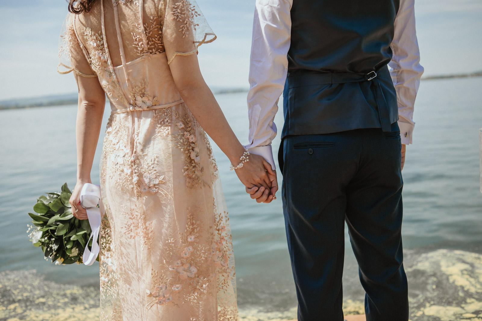 Brautpaar hält sich an der Hand, während Braut Brautstrauss hält
