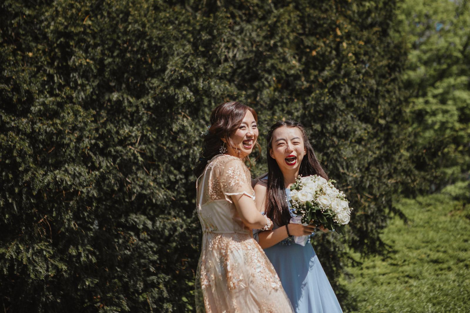 Braut und Frau, die Braustrauss gefangen hat, lachen in Kamera