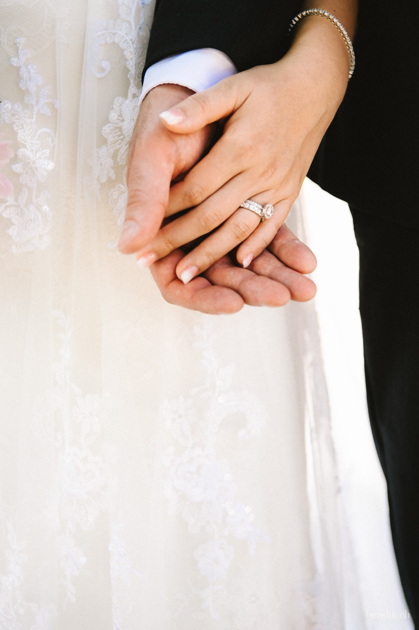 Hände des Brautpaars berühren sich mit sichtbaren Verlobungsring und Trauring