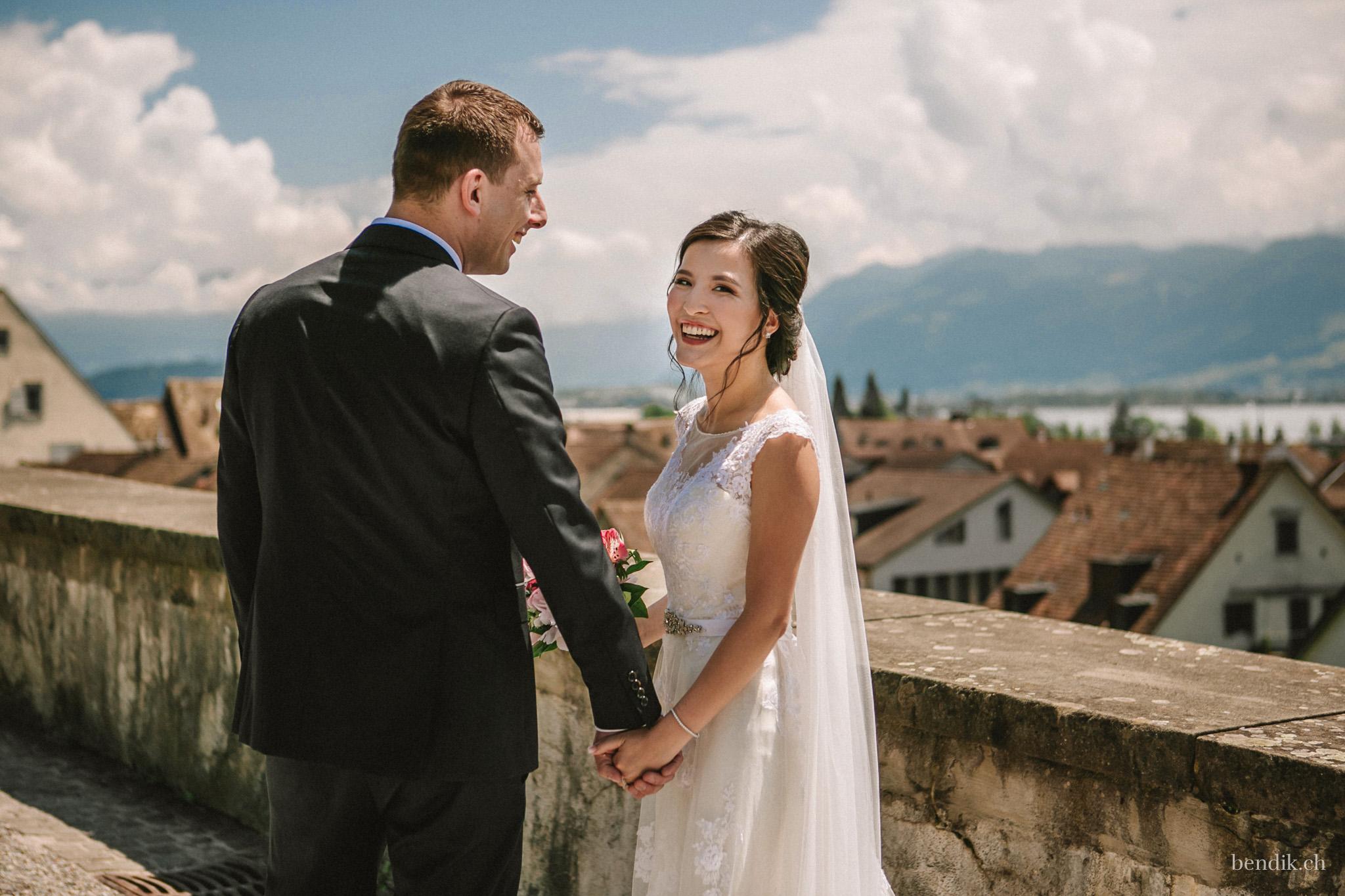 Braut und Bräutigam halten sich lächelnd an der Hand in Rapperswiler Altstadt