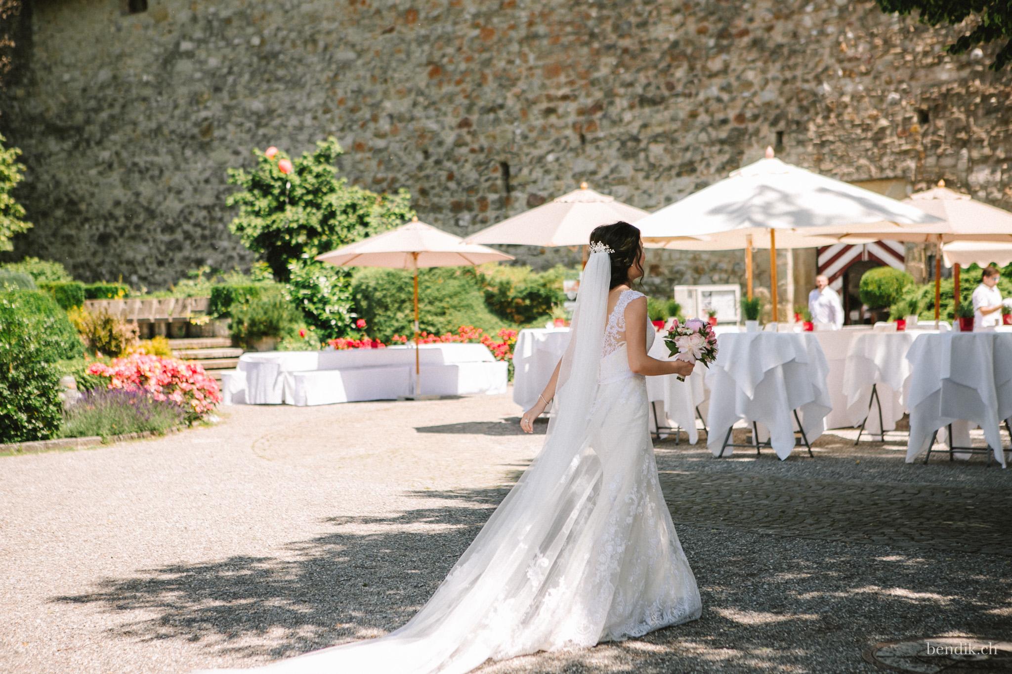 Braut mit weissem Brautkleid und Brautstrauss vor Hochzeitsgedeck
