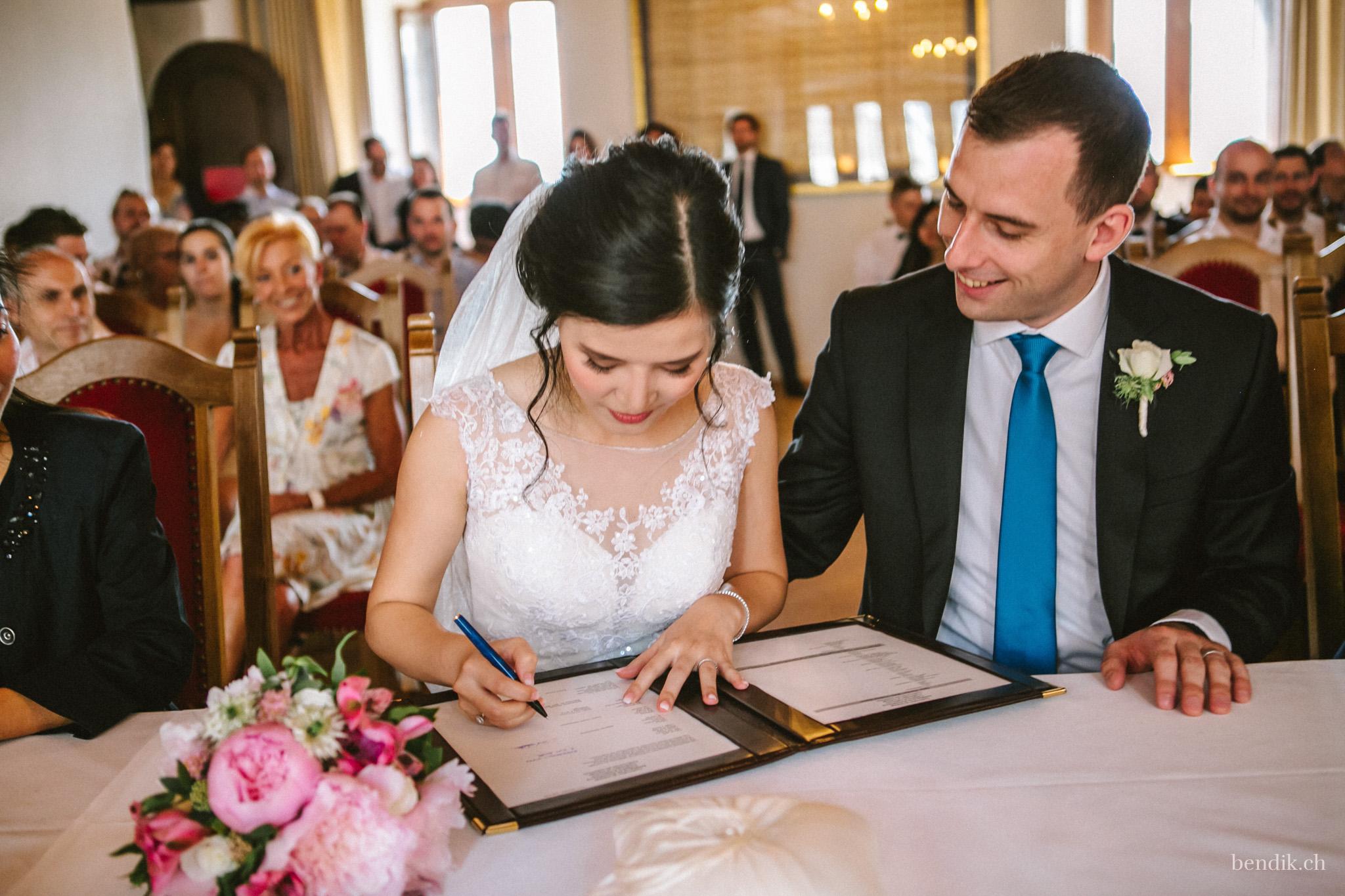 Braut unterschreibt Eheurkunde während Trauung